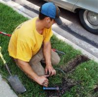 a tech is fixing a broken sprinkler line